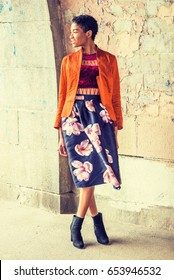 Young African American Woman wearing fashionable orange red jacket, red top, dark blue flower patterned skirt, black boot shoes, standing by painted wall on street in New York, looking away, smiling.