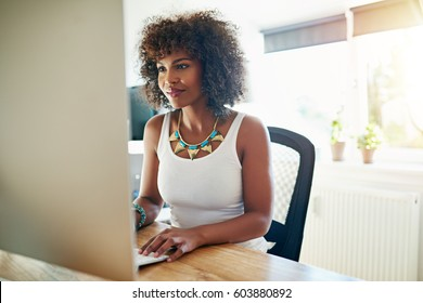 Young African American woman working at a computer in a bright high key home office reading information on her desktop monitor with a smile