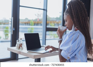 Young african american woman working with laptop and drinking coffee at cafe
