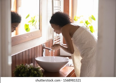 Young african American woman wrapped in towel clean wash face with clear tap water in modern bathroom, biracial female perform daily morning cleanup routine procedure, skincare treatment concept