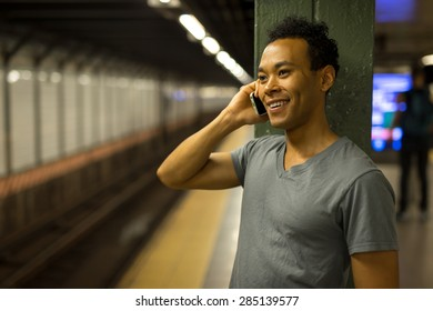 Young African Asian man in New York City in subway station talking on cell phone