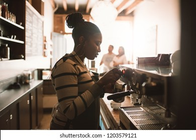 Young African barista frothing milk for a cappuccino hile working behind the counter of her trendy cafe