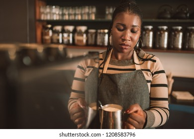 Young African barista frothing milk for a cappuccino behind the counter of her trendy cafe