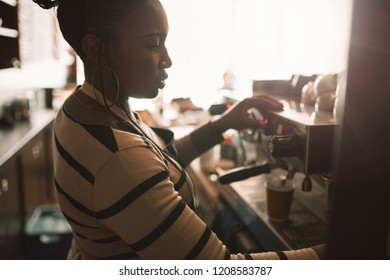 Young African barista pouring fresh coffee into a takeaway cup while working behind the counter of her trendy cafe