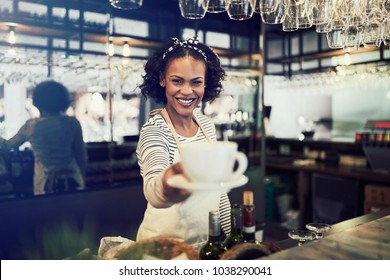 Young African barista smiling while standing behind the counter of a trendy cafe holding up a fresh cup of coffee