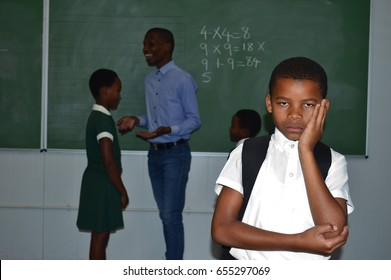 young African black boy looking sad in class wearing uniform