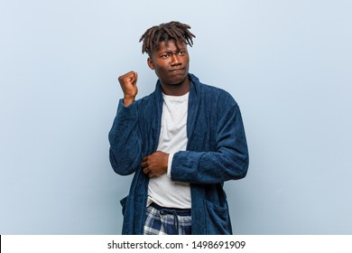 Young african black man wearing pajama touching back of head, thinking and making a choice.