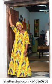 Young African black woman in traditional colorful clothes standing in front of the store