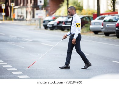 Young African Blind Man Wearing Armband Walking With Stick Crossing Road