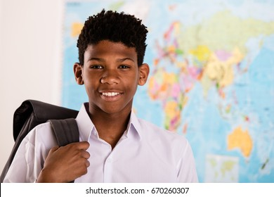 Young African boy in his school uniform and backpack standing in front of a world map grinning happily at the camera