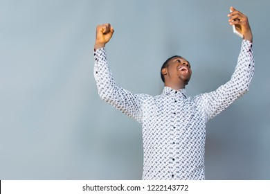 A young African boy with joy on his face with his hands up looking at his phone with surprise .