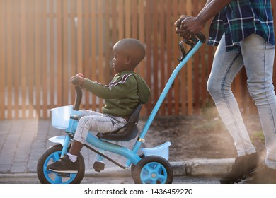 Young african boy kid sitting on tricycle bike bicycle pushed by dad father
