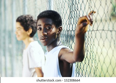 Young African boys  leaning up against a chain link fence