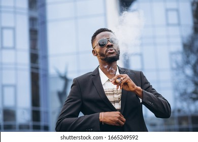 Young african business man in classy suit smoking cigarette