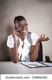 Young african business woman having a conversation on mobile phone with hand gestures