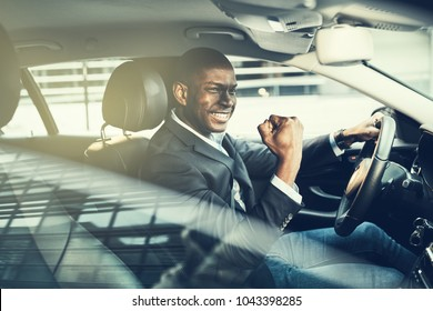 Young African businessman in a blazer celebrating success with a fist pump while driving in a car during his morning commute