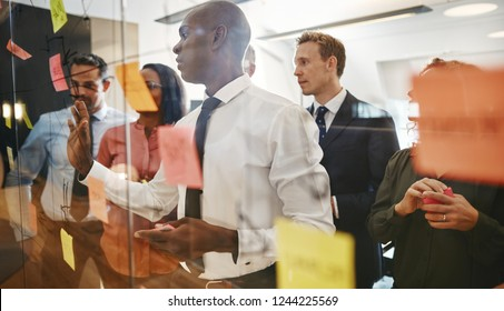 Young African businessman and his team brainstorming with sticky notes on a glass wall while working together in a modern office