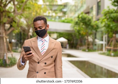 Young African businessman with mask using phone in the city with nature