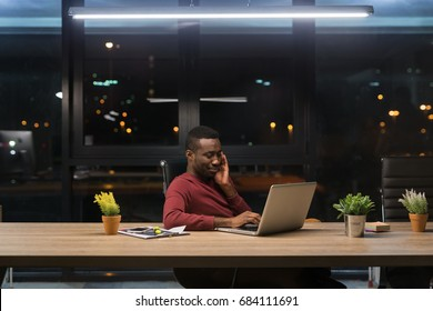 Young african businessman spending time at his office during the night. Concept of doing overtime.