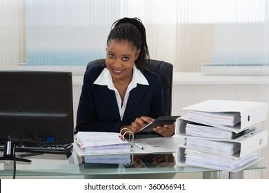 Young African Businesswoman Calculating Bills Using Calculator