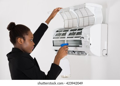 Young African Businesswoman Cleaning Air Conditioner In Office
