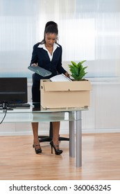 Young African Businesswoman Putting Her Belongings In Box At Office Desk