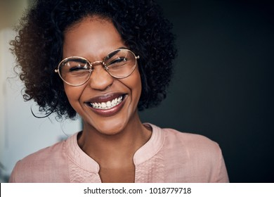 Young African businesswoman wearing glasses and lauging while standing alone in a modern office