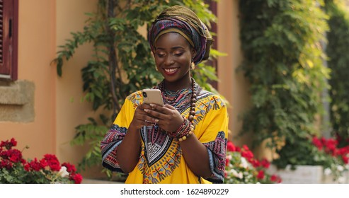 Young African charming smiled woman in traditional clothes standing in nice courtyard with flowers, typing and texting on smartphone.