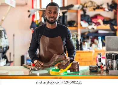 Young African cheerful shoemaker in workshop holding shoes. Looking at camera.