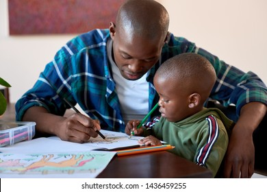 Young african child coloring in book, dad helping him