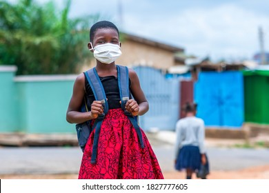 Young African child student in face mask, carrying bag-pack in covid-19 pandemic-concept on education in coronavirus season
