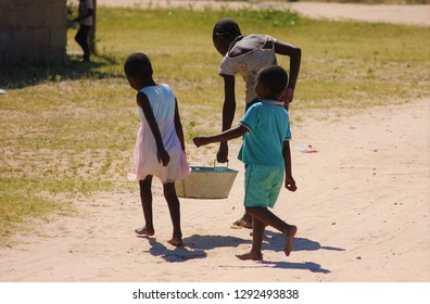 Young African children carry water from the village water tap back home to do their washing.