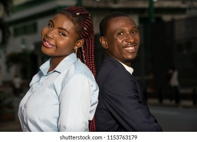 young african couple standing back to back look at camera smiling.