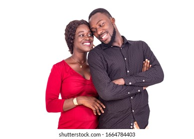 young African couple standing on white background entwined and looking at each other smiling.