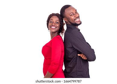 young african couple standing on white background back to back and looking at camera smiling.
