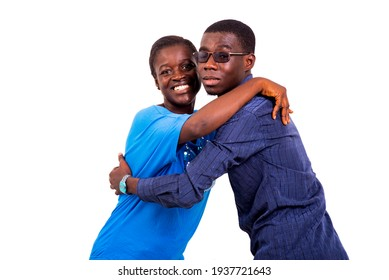 A young African couple standing on a white background looking at the camera smiling.