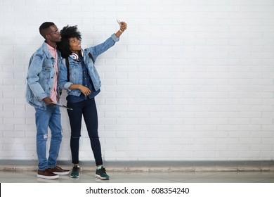Young african couple taking selfie on a mobile phone on white wall background. Hipster men and woman in casual clothes taking mobile photo together
