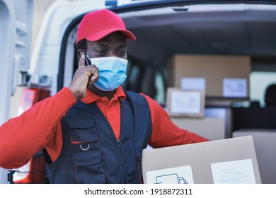 Young african delivery man talking on a call with smartphone while wearing safety mask for coronavirus outbreak