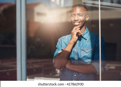 Young African designer looking through window thinking about the future
