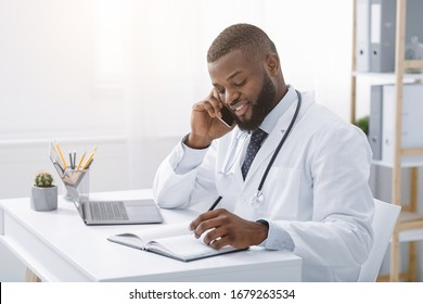 Young african doctor talking to patient on phone while working in modern clinic, high quality service concept