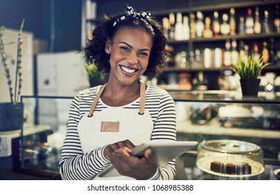 Young African entrepreneur in an apron smiling and using a digital tablet while standing in front of the counter of her trendy cafe
