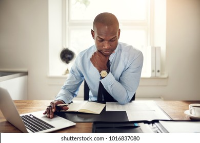 Young African executive reading documents and working on a laptop while sitting at his desk in an office