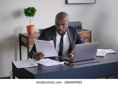 Young African executive reading documents and working on a laptop while sitting at his desk in an office. soft focus