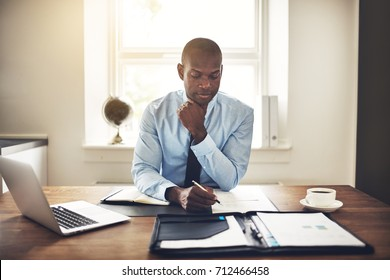 Young African executive sitting at his desk in an office reading documents and working on a laptop