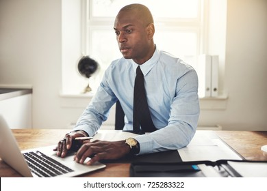 Young African executive wearing a shirt and tie sitting at his desk in an office working online with a laptop