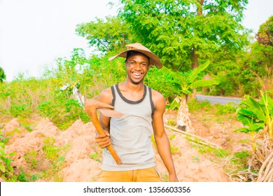 Young African Farmer holding his hoe smiling at camera