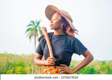 Young African farmer holding a hoe on her shoulder resting