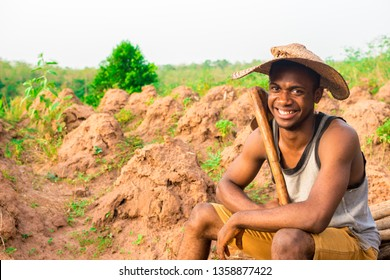 young African farmer sitting down a farm wearing a hat smiling