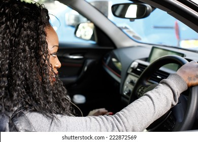 Young African female driver seated behind the wheel of her car, close up profile view of her long curly hair