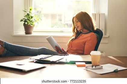Young African female entrepreneur leaning back in a chair in her home office working online with a digital tablet